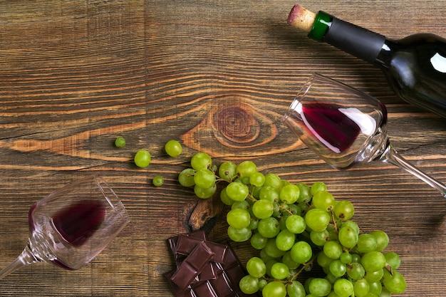 Botella de vino tinto, chocolate de uva y vasos sobre la vista superior de la mesa de madera con espacio de copia