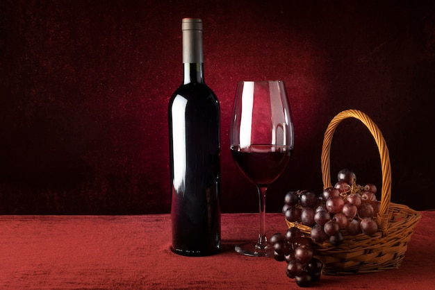 Botella de vino tinto y copa con cesta de uvas