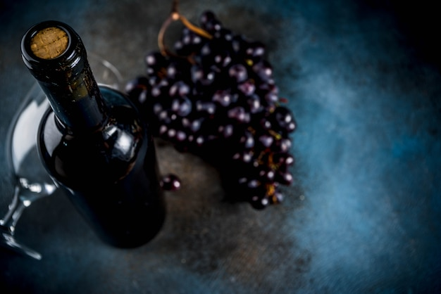 Botella de vino tinto con copa y uvas