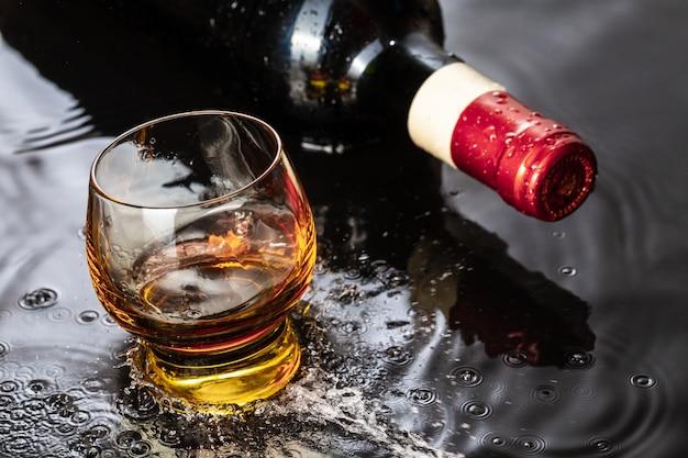 Botella de vino tinto con copa de vino. salpicaduras de agua y gotas sobre el reflejo negro.