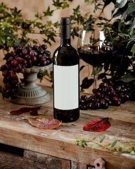 Botella de vino tinto y una copa de vino tinto