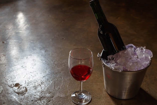 Botella de vino tinto en un cubo de hielo y una copa de vino tinto