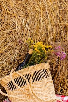 Botella de vino tinto, dos copas y flores silvestres en canasta en el campo y gavilla
