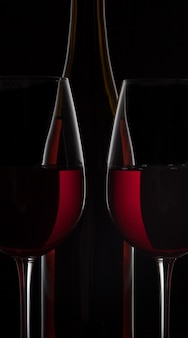 Botella de vino tinto y dos copas de vino en negro