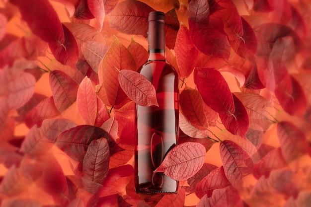 Una botella de vino tinto o rosado sobre un fondo de hojas de otoño, foto de primer plano horizontal.