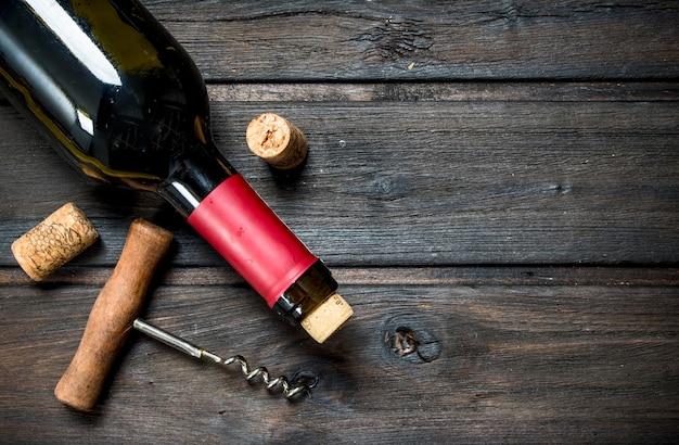 Botella de vino tinto con un sacacorchos sobre una mesa de madera.