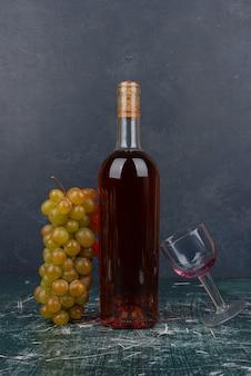 Botella de vino tinto y uvas en mesa de mármol.