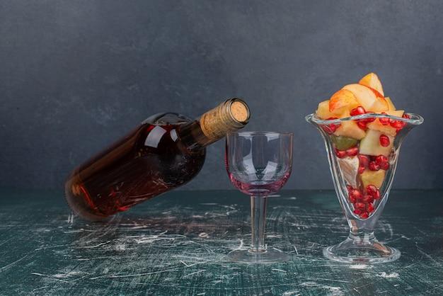 Botella de vino tinto, uvas y vaso de frutas mixtas sobre mesa de mármol