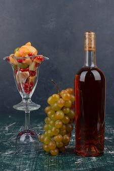 Botella de vino tinto, uvas y vaso de frutas mixtas sobre mesa de mármol.