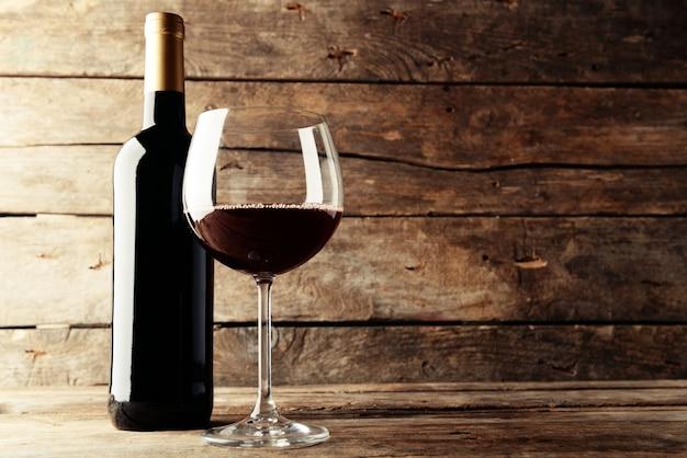 Una botella de vino tinto y un vaso de mesa de madera