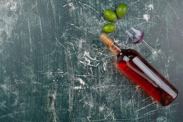 Botella de vino tinto y vaso sobre mesa de mármol con feijoas
