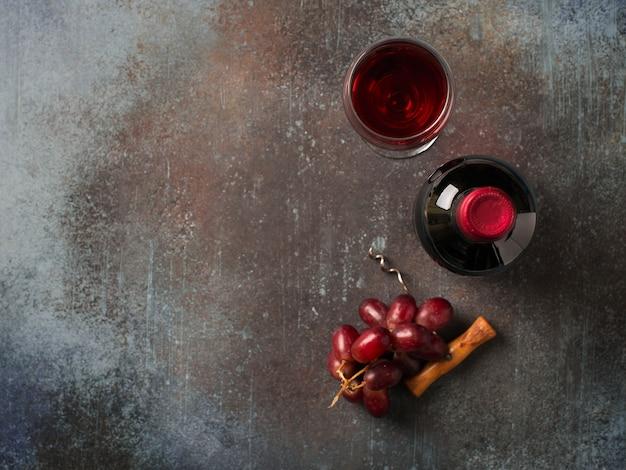 Botella de vino tinto con vasos con bebida y uvas sobre fondo oscuro, vista superior, espacio de copia
