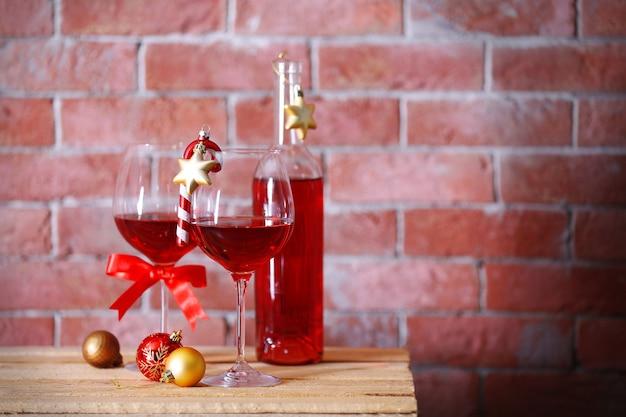 Botella de vino tinto y vasos con regalos de navidad en la pared