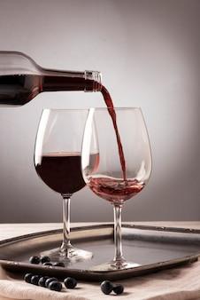 Botella de vino tinto vertiendo líquido en vidrio