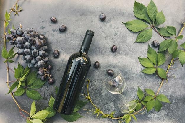 Botella de vino tinto, vid verde, copa de vino y uva madura sobre fondo de mesa de piedra oscura vintage. espacio de copia de vista superior para texto. tienda de vinos, bar de vinos, bodega o concepto de cata de vinos.