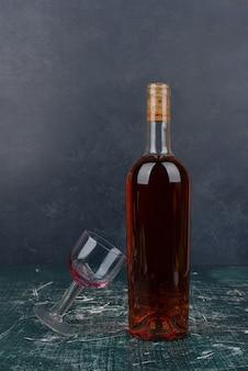 Botella de vino tinto y vidrio sobre mesa de mármol