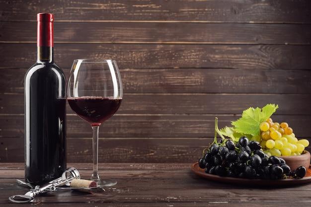 Botella de vino y uva en mesa de madera