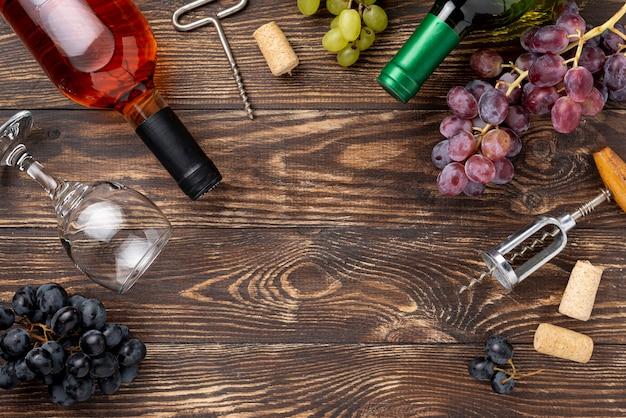 Botella de vino, uvas y copas en la mesa