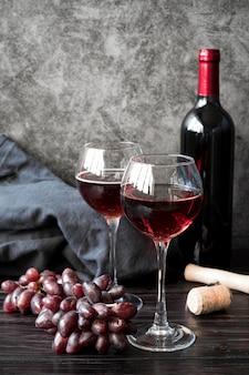Botella de vino con uvas de vista frontal