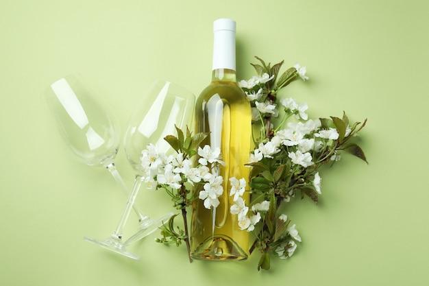 Botella de vino, vasos y flores sobre fondo verde