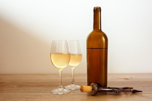Botella de vino y vasos llenos con sacacorchos