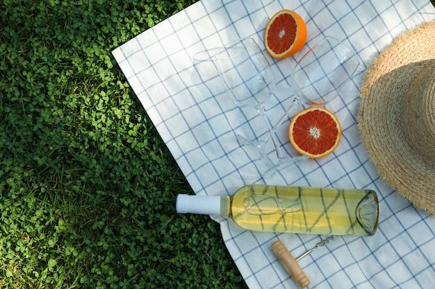 Botella de vino, vasos, naranja, sacacorchos, toalla y sombrero de paja sobre hierba