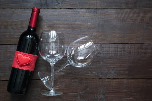 Botella de vino y vasos sobre tabla de madera. vista superior con espacio.
