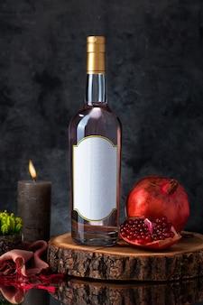 Botella de vino con vela, granada, planta y bufanda sobre una pieza de madera.