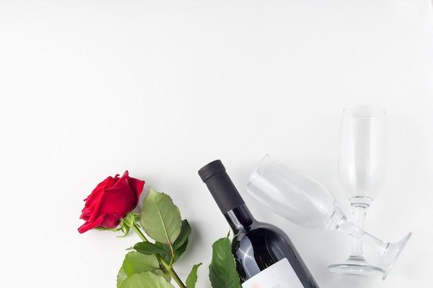 Botella de vino, vidrio y rosa roja con pétalos sobre un fondo blanco aislado
