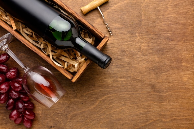 Botella de vino de vista superior y vaso con uvas y espacio de copia