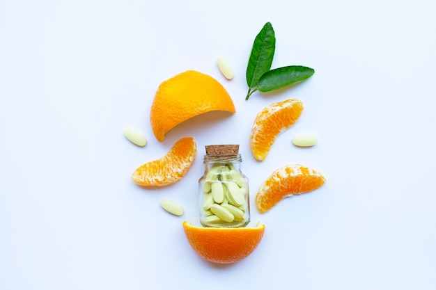 Botella de vitamina c y pastillas con fruta naranja sobre blanco