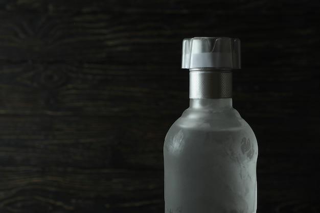 Botella de vodka en blanco sobre mesa de madera