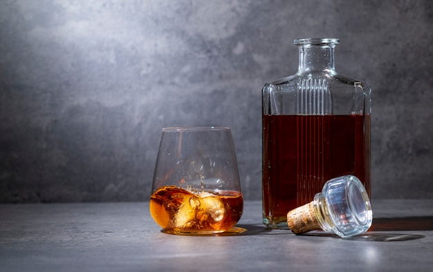 Botella de whisky cuadrada y vaso con hielo sobre la superficie de cemento gris oscuro