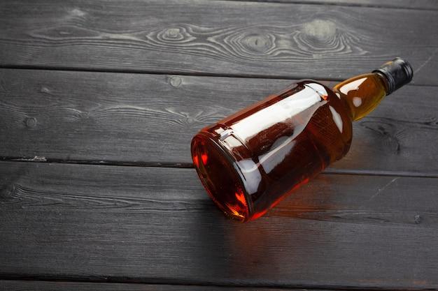 Botella de whisky en endecha plana de madera oscura