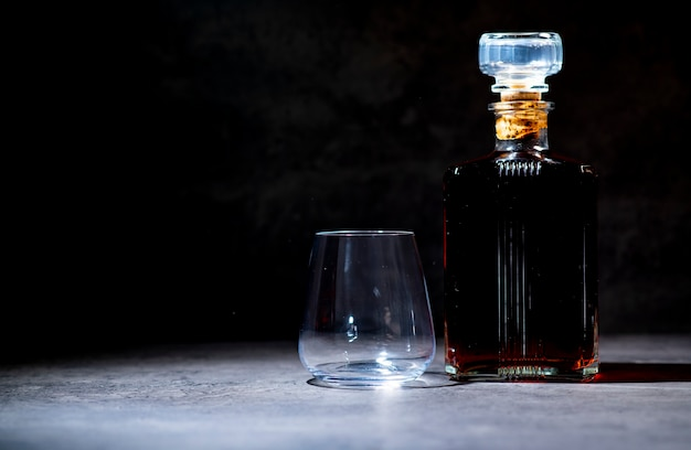 Una botella de whisky en forma cuadrada en los rayos de luz junto a un vaso vacío sobre una superficie de cemento gris oscuro
