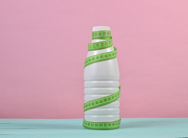 Botella de yogurt envuelto en una regla sobre un fondo rosa, concepto dietético, adelgazante