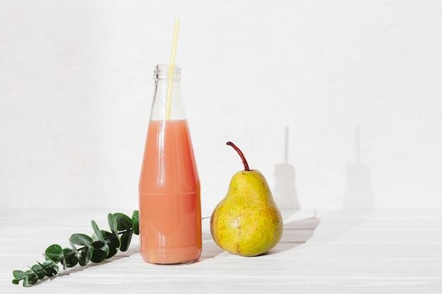Botella de zumo con pera y hojas.