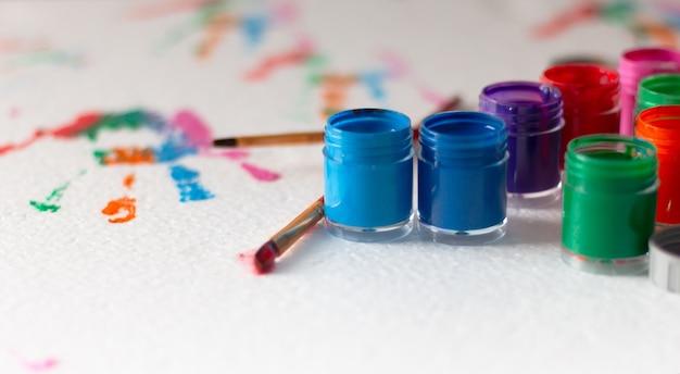 Botellas abiertas de color de cartel y pincel sobre fondo blanco