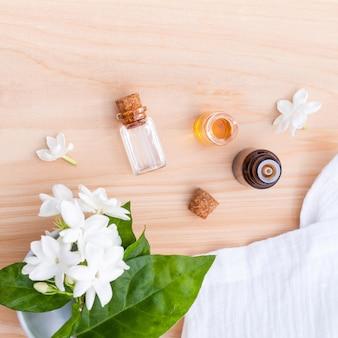 Botellas de aceite de aroma dispuestas con flores de jazmín sobre fondo de madera.