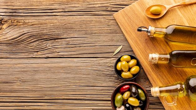 Botellas de aceite, cuencos de oliva y cuchara de madera con espacio de copia