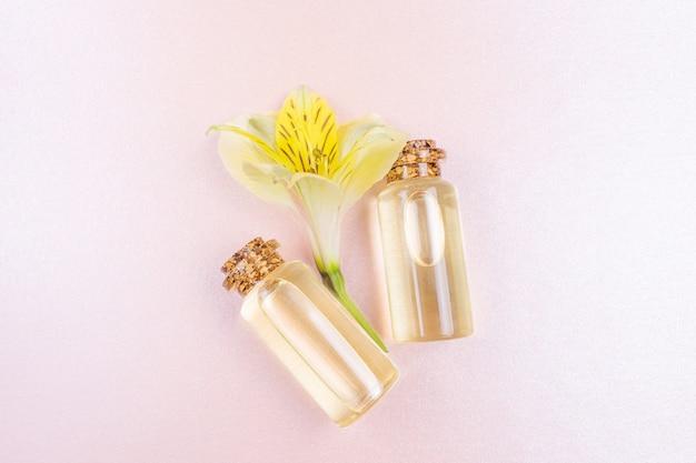 Botellas con aceite esencial floral y una flor amarilla en rosa pastel