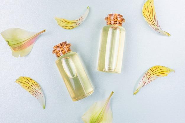 Botellas con aceite esencial floral y pétalos de flores amarillas sobre blanco