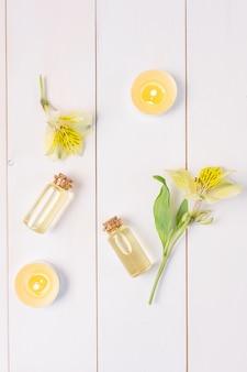 Botellas con aceite esencial floral sobre una madera blanca.