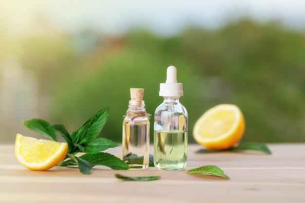 Botellas con aceite de menta, limón y hojas de menta verde fresca en la mesa de madera. fondo desenfocado