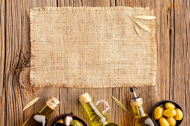 Botellas de aceite de oliva con aceitunas y maqueta textil
