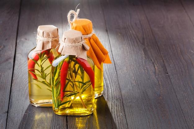 Botellas de aceite de oliva virgen extra con hierbas aromáticas.