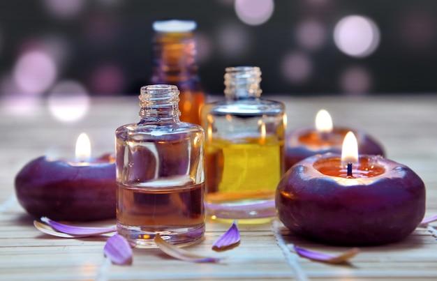 Botellas de aceite y velas en luces borrosas