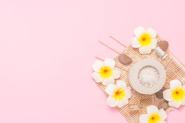 Botellas con aceites aromáticos, sal marina, flores tropicales plumeria sobre una superficie rosa. concepto de tratamientos de spa, sauna, masajes. vista plana, vista superior.