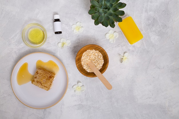 Botellas de aceites esenciales; avena; planta de cactus; jabón amarillo y panal sobre fondo de hormigón