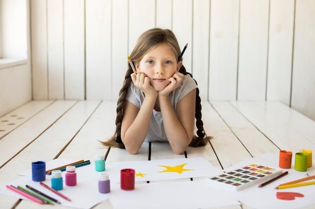 Botellas de acuarela y lápices de colores frente a una chica con pincel en la mano mirando a la cámara